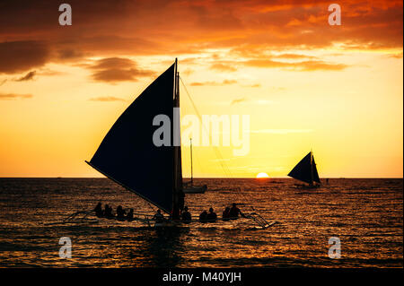 Dramatic orange sea sunset with sailboat in tropical country, clouds. Wide angle. silhouettes of boats, the solar - Stock Photo