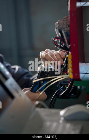 Hands of electrician with stripper installing energy system on machinery industry - Stock Photo