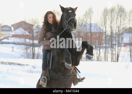 Young woman riding on black horse in snowy countryside - steed stood on its hind legs - Stock Photo