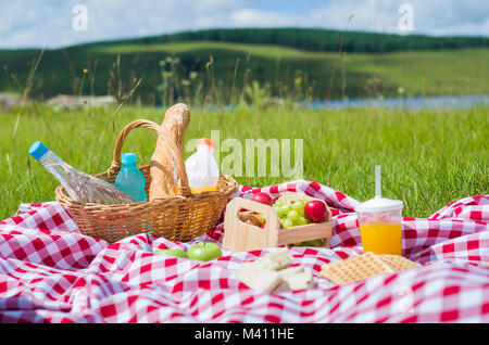 Great concept of pic-nic, pic-nic with fruits and juice on green lawn with beautiful view - Stock Photo