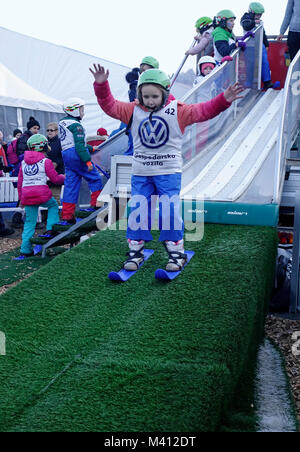A young girl lands after the jump on the 'baby ski jumping hill' for children. Ljubno ob Savinji, Slovenia. - Stock Photo