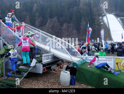 Young kids play on the 'baby ski jumping hill' for children. Ljubno ob Savinji, Slovenia. - Stock Photo