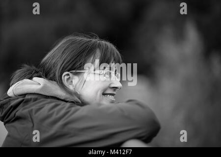 Mono portrait of happy caucasian female (side-on) in glasses resting chin on hands, casually leaning on bridge, - Stock Photo