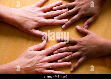 looking down on four fifty year old female hands spread out, lying flat on a table, the two hands on the left a - Stock Photo
