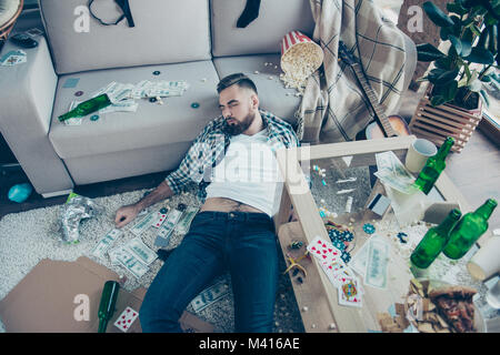 After party consequences. Top view above photo of drunk bearded wearing checkered shirt and jeans, he is sleeping - Stock Photo