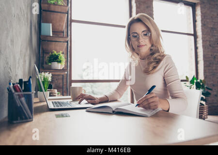 Portrait of beautiful confident with blonde curly hair clever woman wearing casual clothes, she is sitting at the - Stock Photo