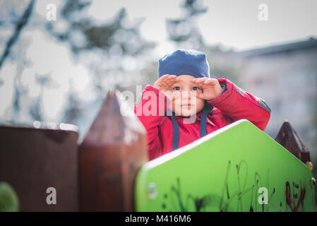 Adorable toddler boy playing on a fort in the park - Stock Photo