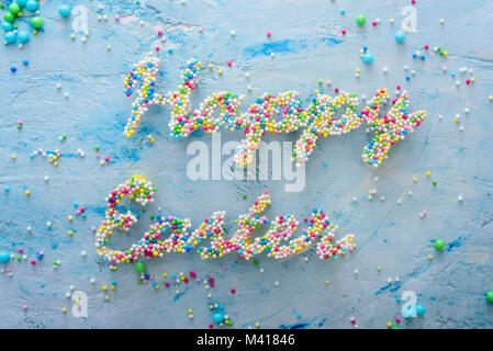 Words Happy Easter made of colorful candies on blue pastel background - Stock Photo