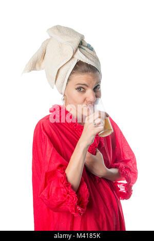 Girl in bathrobes drinking orange juice - Stock Photo