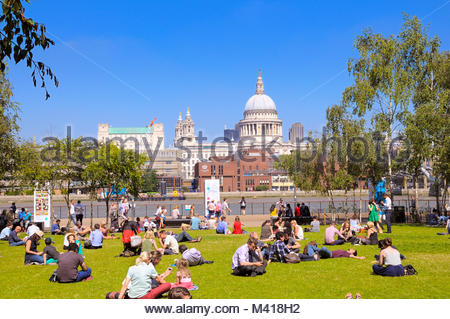 People relaxing in Tate Modern gardens opposite St Paul's Cathedral, London, England, UK - Stock Photo