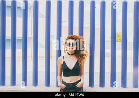 Young redhead model and a blue background - Stock Photo
