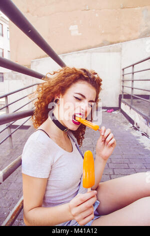 Redhead young woman eating ice creams in summer - Stock Photo