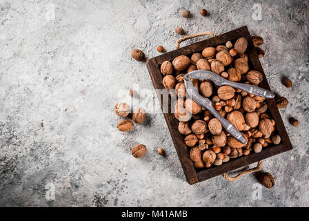 Various nuts and nutcracker in wooden box. On rustic grey stone table, copy space - Stock Photo