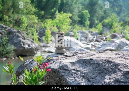 Stones pyramid on rock symbolizing stability, zen, harmony, balance. - Stock Photo