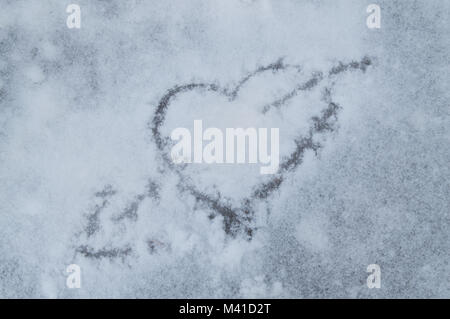 Valentine's day. Heart pierced by an arrow drawn on snow. - Stock Photo