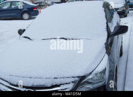 The parked car is on the road, covered with snow - Stock Photo