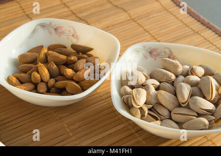 Two bowls of almonds and pistachios. Healthy meals snacks. - Stock Photo