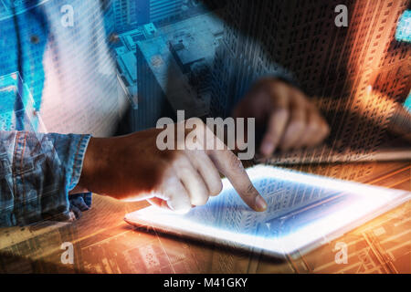 Young person touching the screen of a tablet while working - Stock Photo