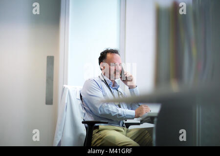 Male Medical Doctor on phone in his office - Stock Photo