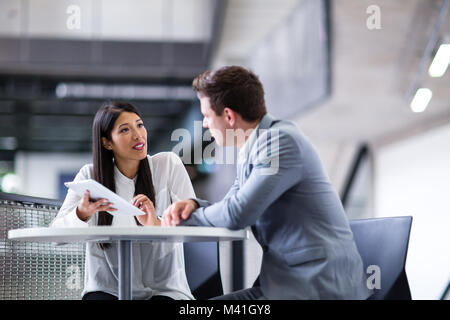 Colleagues in an informal business meeting using a digital tablet - Stock Photo