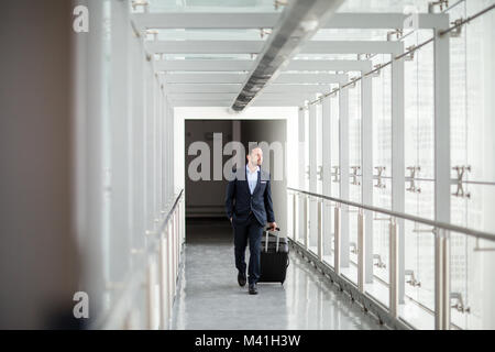 Businessman walking through airport terminal - Stock Photo