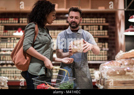 Baker helping customer in grocery store - Stock Photo