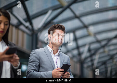 Businessman listening to podcast waiting for train at station - Stock Photo