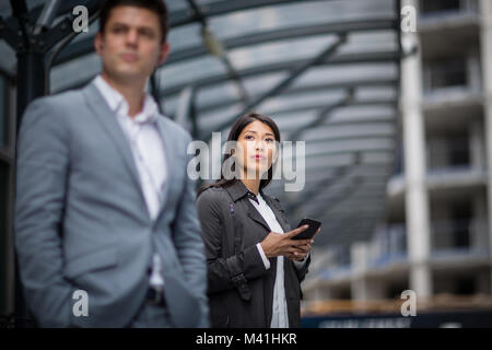 Businesswoman waiting for train on platform with smartphone in hand - Stock Photo