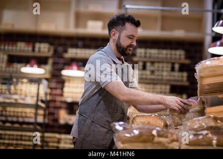 Baker in bakery stocking shelves and looking to camera - Stock Photo