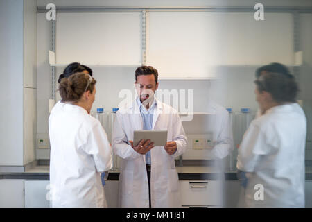 Team of scientists discussing experiment data on digital tablet - Stock Photo