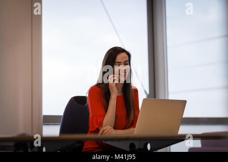 Female executive working on laptop and using smartphone - Stock Photo