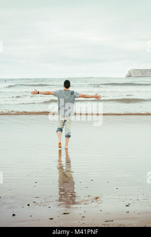 Young man enjoying the day in the beach - Stock Photo