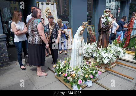 Statues are lined up on the pavement before the procession of Our Lady of Mount Carmel from the Italian Church in - Stock Photo