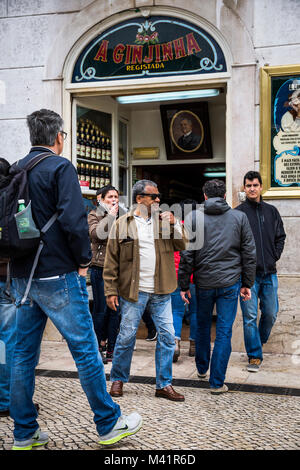 People drink ginjinha in Lisbon, Portugal. - Stock Photo