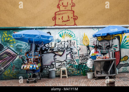 A street scene of a woman with two stalls selling items in front of a wall covered in graffiti in Bogota, Colombia - Stock Photo