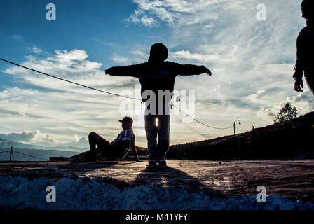 A young boy silhouetted against the blue sky standing with his arms out with two other boys at sunset - Stock Photo
