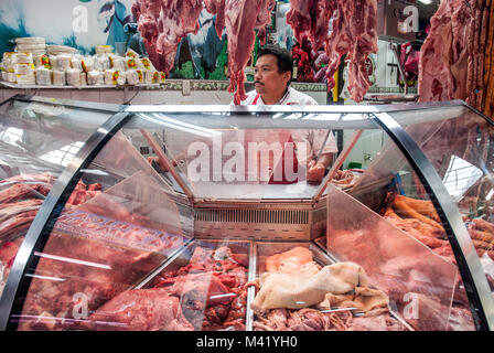 A butcher standing behind his meat counter holding a knife at a market in Bogota, Colombia - Stock Photo