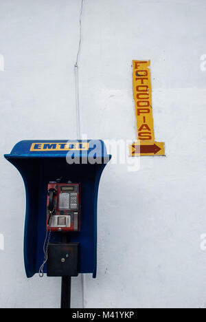 A blue public phone in front of a white wall with a yellow sign saying ´photocopies´ in Spanish - Stock Photo