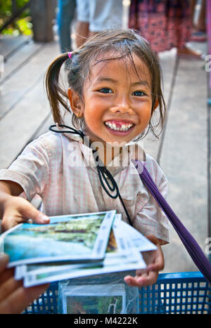 SIEM REAP, CAMBODIA - NOV 21, 2013: An unidentified cambodian girl street seller in Angkor Wat, Nov 21, 2013 on - Stock Photo