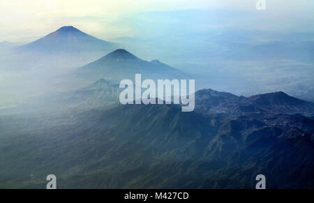 Volcano over Java Island as seen from airplane window. The landscape shows mount Sindoro, mount Sumbing and Dieng - Stock Photo