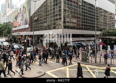 Hong Kong - February 2 2018: People cross the busy street in front of the Wanchai MRT station in Hong Kong island, - Stock Photo