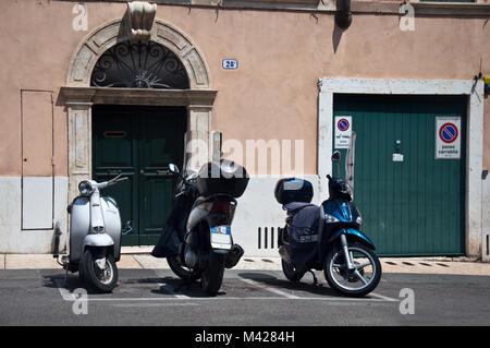 Three motor cycles parked in designated parkinig bays, Verona, Italy - Stock Photo