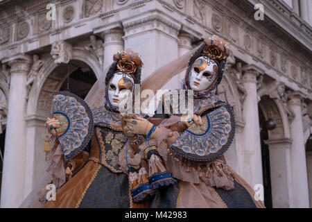 Two women in traditional costumes and masks, with decorated fans, standing in front of the arches at St Marks Square - Stock Photo