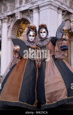 Two women in hand sewn costumes and hand painted masks, with decorated fans, standing in front of the arches at - Stock Photo