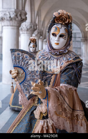 Woman holding fan and wearing colorful mask and ornate costume under the arches at the Doges Palace during Venice - Stock Photo