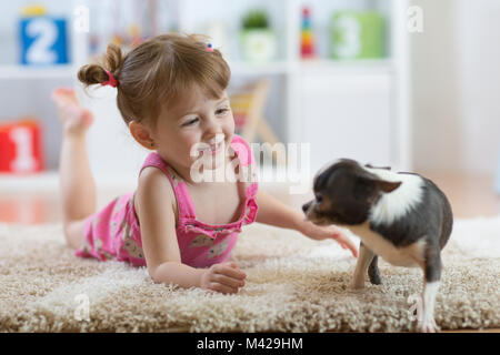 The child playing with the dog lying on floor at home - Stock Photo