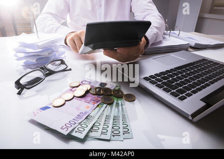 Close-up Of A Businessman Using Calculator With Euro Currencies And Laptop On Desk - Stock Photo