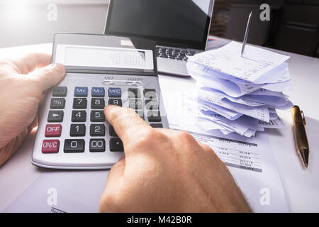 Close-up Of A Person's Hand Calculating Invoice Near Bills And Laptop In Office - Stock Photo