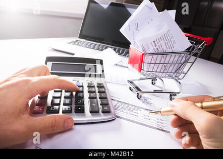 Close-up Of Person Calculating Invoice With Calculator Near Shopping Cart On Desk - Stock Photo