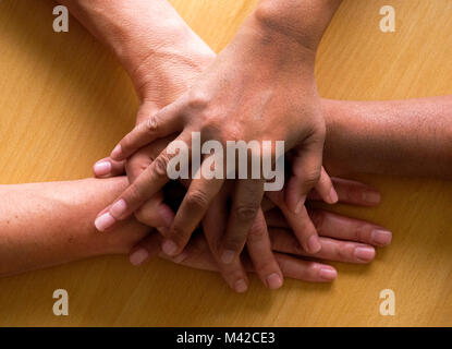 looking down on four fifty year old female hands placed ontop of each other, the top hand and third hand are Asian - Stock Photo